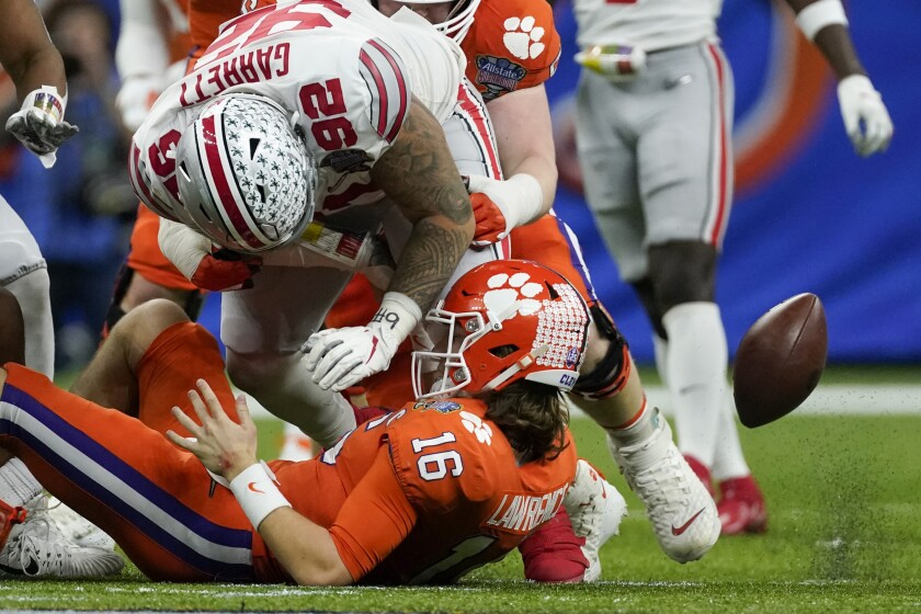 Ohio State defensive tackle Haskell Garrett forces a fumble by Clemson quarterback Trevor Lawrence during the second half of the Sugar Bowl NCAA college football game Friday, Jan. 1, 2021, in New Orleans. (AP Photo/John Bazemore)