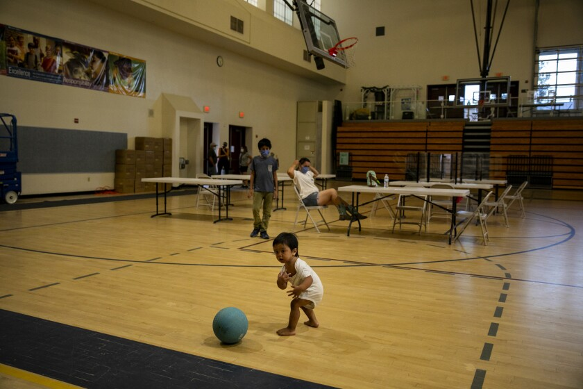 Felipe Arrieta, who is almost two years old, plays with a ball at an evacuation center at MacQueen Middle School.