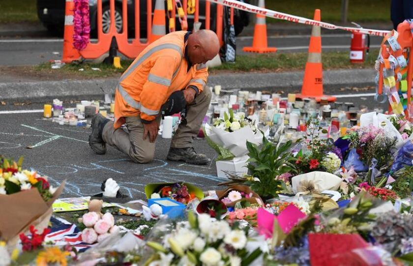 A worker grieves at a makeshift memorial at the Al Noor Mosque on Deans Rd in Christchurch, New Zealand, Mar. 19, 2019. EPA-EFE/MICK TSIKAS AUSTRALIA AND NEW ZEALAND OUT
