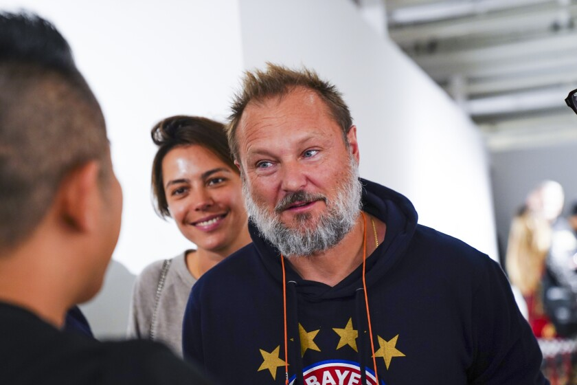 Juergen Teller, wearing a dark hoodie, chats with people in 2019