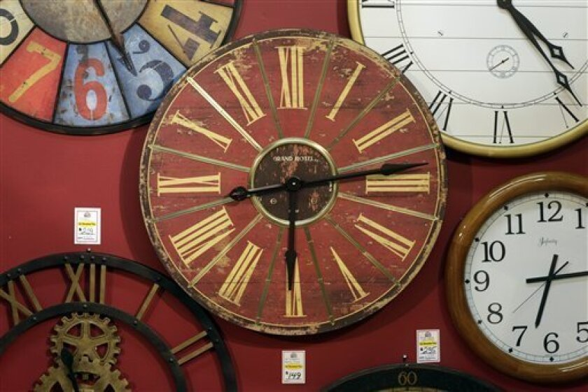 Clocks hang on a wall in Hands of Time, a clock store and repair shop in Savage, Md., Friday, March 8, 2013. It's the weekend to spring ahead for daylight saving time. Officially, the change starts Sunday at 2 a.m., and most Americans will get an hour less sleep but will gain an hour more of evening sunlight in the coming months. Not every place makes the switch. The exceptions are Hawaii, most of Arizona, Puerto Rico, the Virgin Islands, American Samoa, Guam and the Northern Marianas. (AP Photo