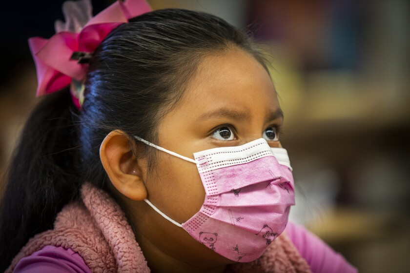A young student wears a pink mask with a panda print
