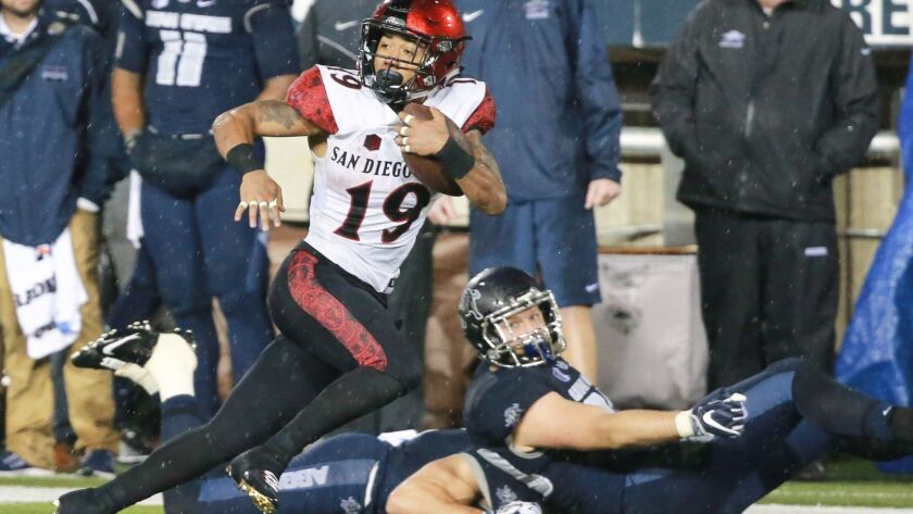 The Aztecs' D.J. rushes for some of his 223 yards on Thursday night against Utah State, a game played in a downpour most of the night.