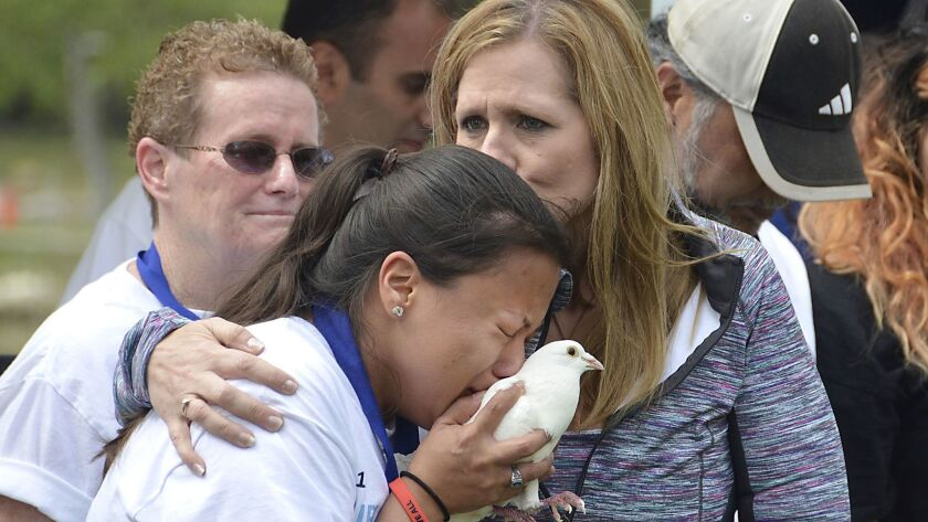 Patricia Wenskunas, founder and CEO of Crime Survivors, Inc. hugs one of the victims during a dove r