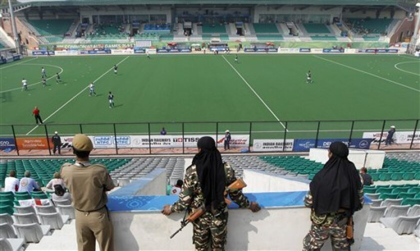 Indian security personnel watch the Commonwealth Games field hockey match between Pakistan and Scotland in a poorly filled Major Dhyan Chand National Stadium in New Delhi, India, Tuesday, Oct. 5, 2010. The empty stadiums that marred the first day of competition at the crisis-hit Commonwealth Games may be filled by children and the underprivileged if attendance doesn't improve. (AP Photo/Eranga Jayawardena)