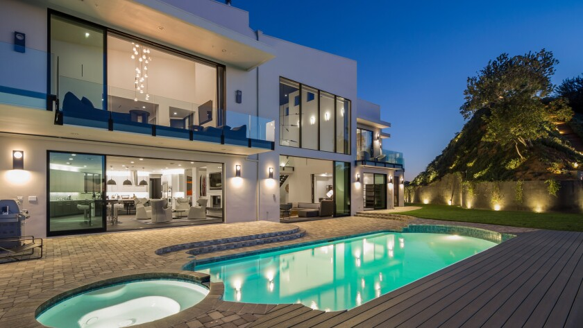 The three-story Contemporary-style house sits on close to an acre behind gates in Beverly Hills.