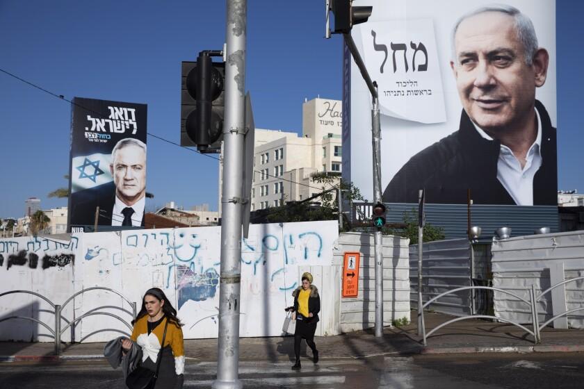 People walk next to election campaign billboards last month showing Israeli Prime Minister Benjamin Netanyahu, right, and Benny Gantz, left, in Bnei Brak, Israel.