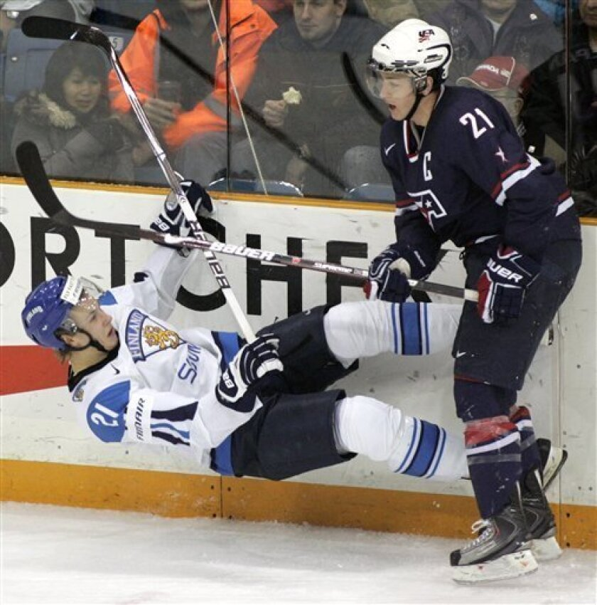 Team Finland's Jasse Ikonen, left, is checked to the ice by Team USA's Derek Stepan during the second period of a quarter final hockey game at the world junior hockey championship on Saturday, Jan. 2, 2010 in Saskatoon, Saskatchewan. (AP Photo/The Canadian Press, Geoff Howe)