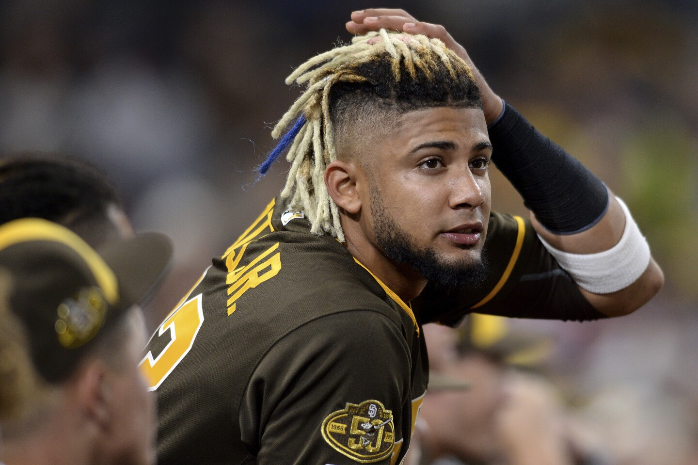 San Diego Padres' Fernando Tatis Jr. looks on from the dugout during the sixth inning of the baseball game against the Colorado Rockies Friday, Aug. 9, 2019, in San Diego. (AP Photo/Orlando Ramirez)