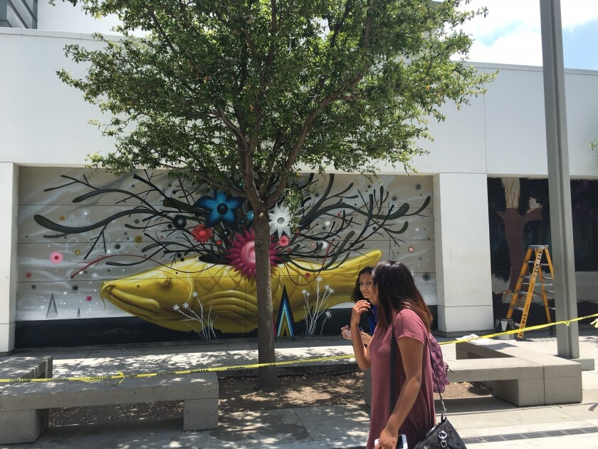 Students pass a mural by L.A. artist Jeff Soto.