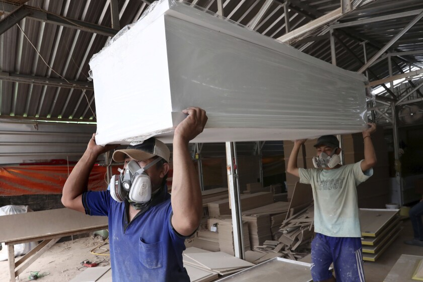 Workers in protective face masks carry coffins built for those who died from the coronavirus at a factory in Serpong, outside Jakarta, Indonesia.