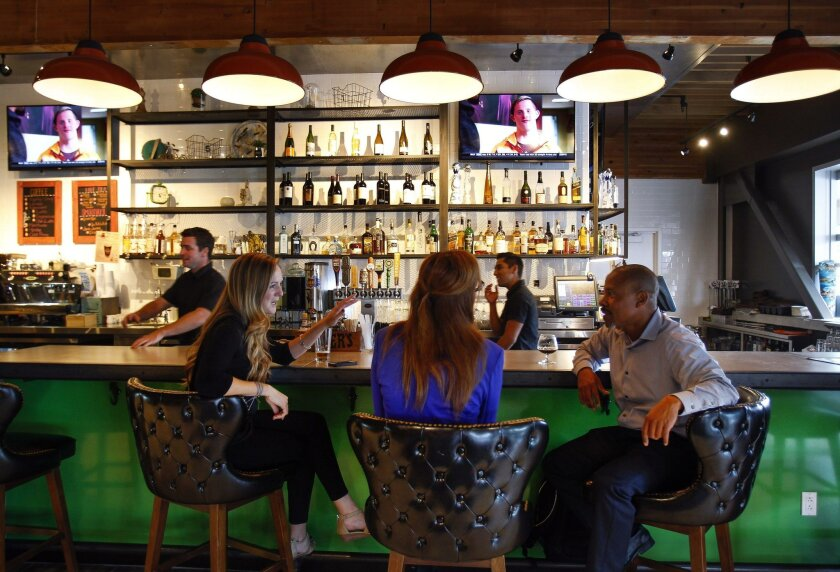 Heather Ramsey, left, Melanie Nally, both with Biocom, and Brian Landrum, with Airgas, sit at the bar in the Farmer & Seahorse restaurant and bar at the Alexandria in Torrey Pines Mesa.