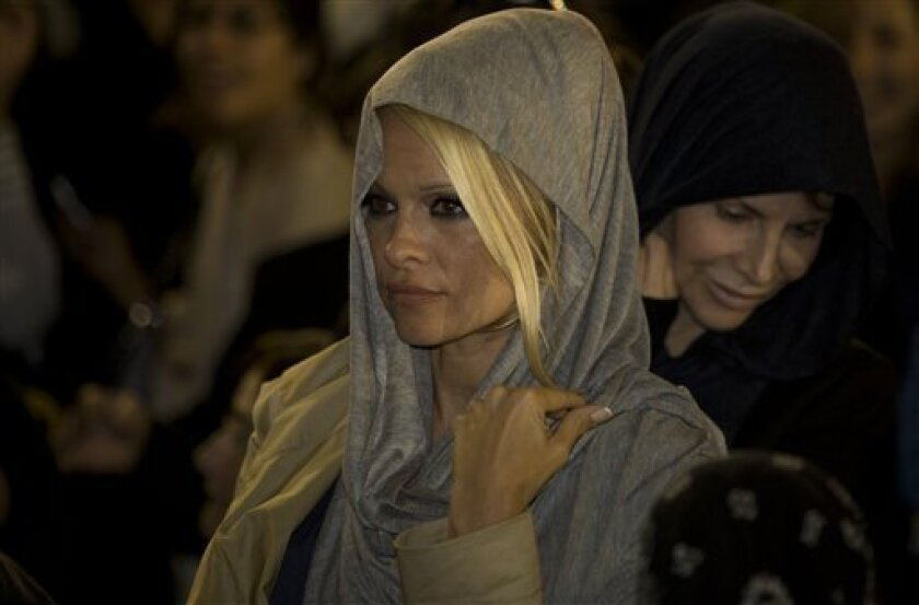"U.S. actress Pamela Anderson is seen at the Western Wall, Judiasm's holiest site, in Jerusalem's Old City, Sunday, Nov. 7, 2010. Former ""Baywatch"" star Pamela Anderson said Sunday she will try her powers of seduction while in Israel on an unlikely audience, ultra-Orthodox Jewish lawmakers. Anderson, an honorary director of People for the Ethical Treatment of Animals, is in Israel to participate in the local version of ""Dancing with the Stars."" (AP Photo/Sebastan Scheiner)"