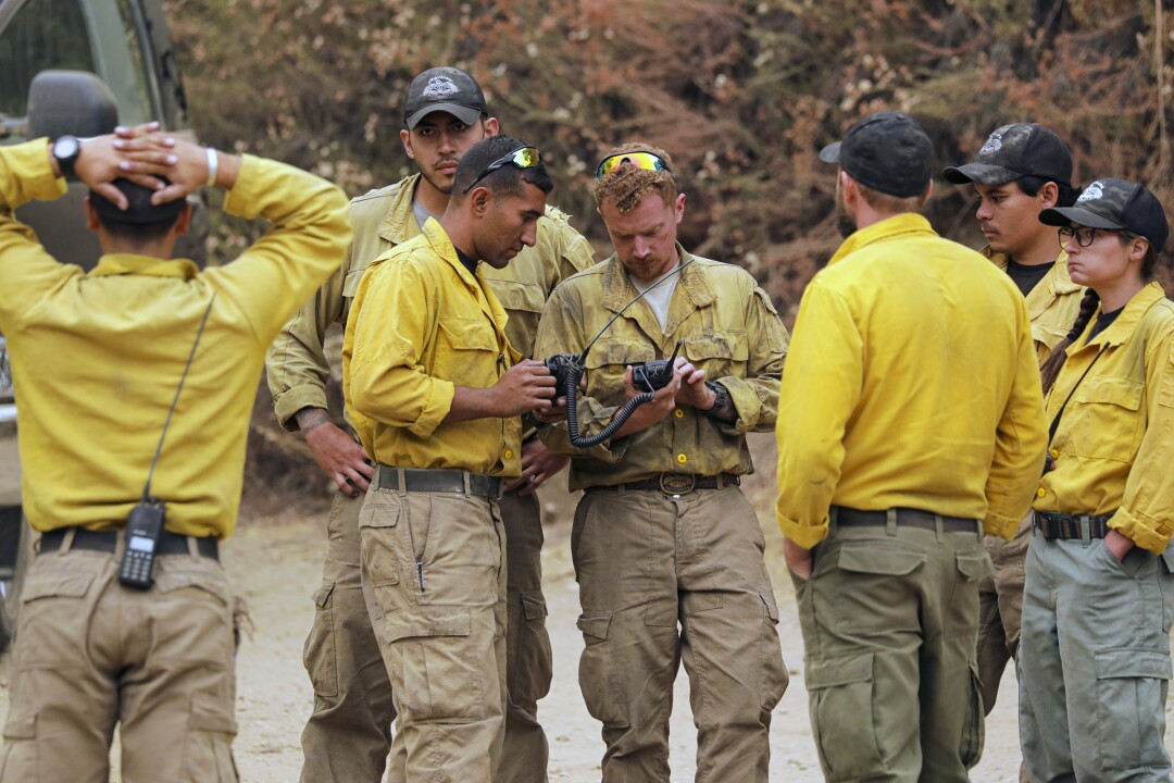 Fire hotshot crew Aravaipa huddle to plan their attack on the Bobcat fire