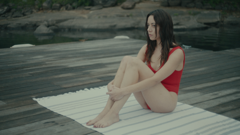 "Aubrey Plaza, in a bathing suit, sits on a towel in the movie ""Black Bear."""