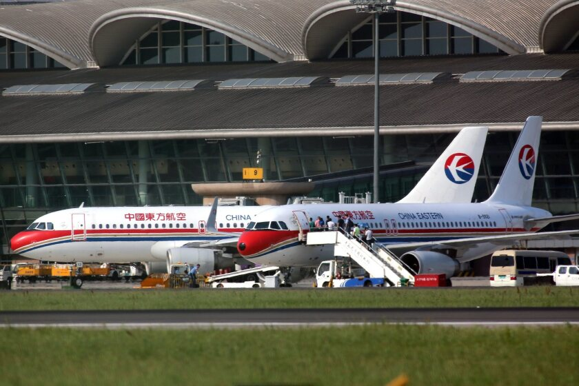 Passengers board a China Eastern Airlines flight on June 14 at an airport of Qingdao, one of 11 Chinese cities that a flight attendants' group says will be affected by flight delays through Aug. 15.