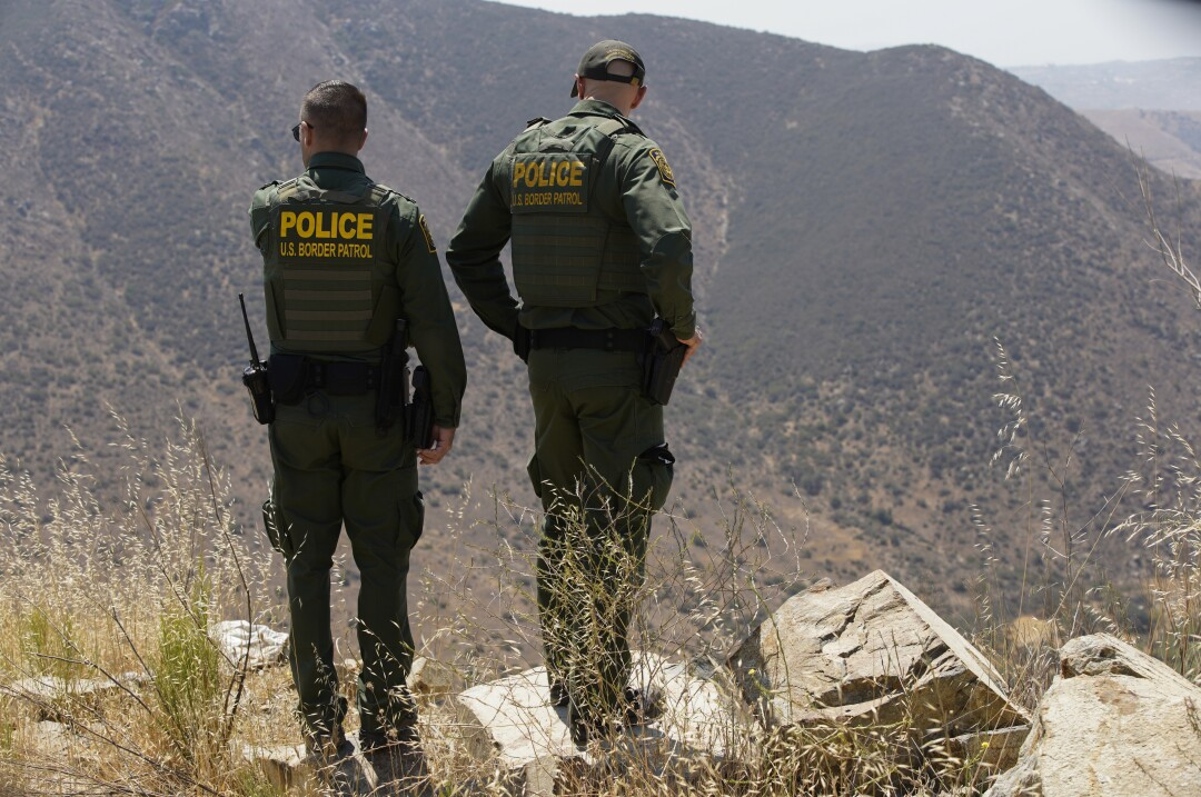 Border Patrol agents Jeff Stephenson and Jacob Macisaac look down from Otay Mountain on Tuesday, June 8.