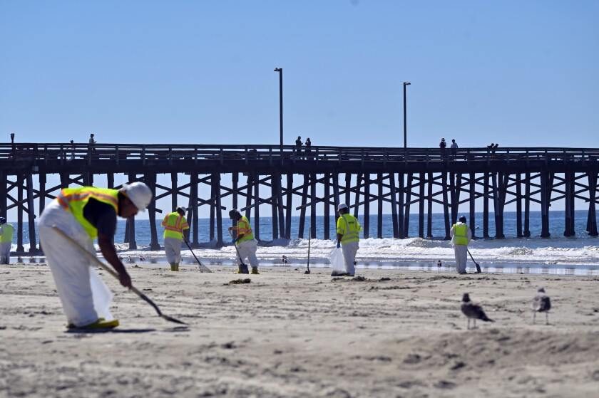 Workers clean oil from the sand, south of the pier, in Newport Beach, Calif., Tuesday, Oct. 5, 2021. A leak in an oil pipeline caused a spill off the coast of Southern California, sending about 126,000 gallons of oil into the ocean, some ending up on beaches in Orange County. (Jeff Gritchen/The Orange County Register via AP)