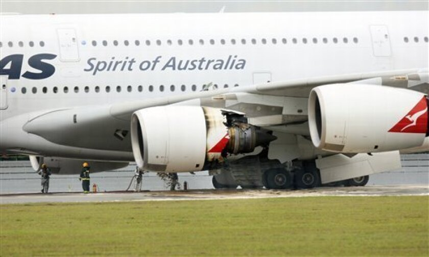 Firefighters surround a Qantas passenger plane which made an emergency landing in Singapore's Changi International Airport after having engine problems on Thursday Nov. 4, 2010 in Singapore. (AP Photo/Wong Maye-E)
