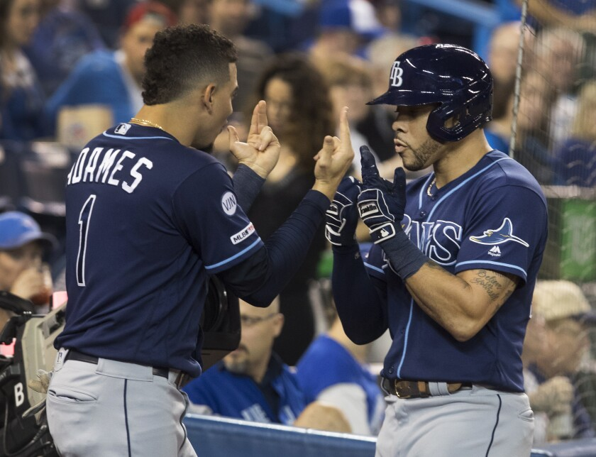 Tampa Bay Rays' Tommy Pham, right, is greeted by Willy Adames (1) after he hit a two-run home run against the Toronto Blue Jays in the third inning of a baseball game in Toronto on Friday, Sept. 27, 2019. (Fred Thornhill/The Canadian Press via AP)
