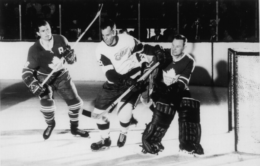 Gordie Howe of the Detroit Red Wings skates between defenseman Allan Stanley and goalie Johnny Bower of the Toronto Maple Leafs during Game 5 of the 1963 Stanley Cup Final at Maple Leaf Gardens. The Maple Leafs won the game and the series.