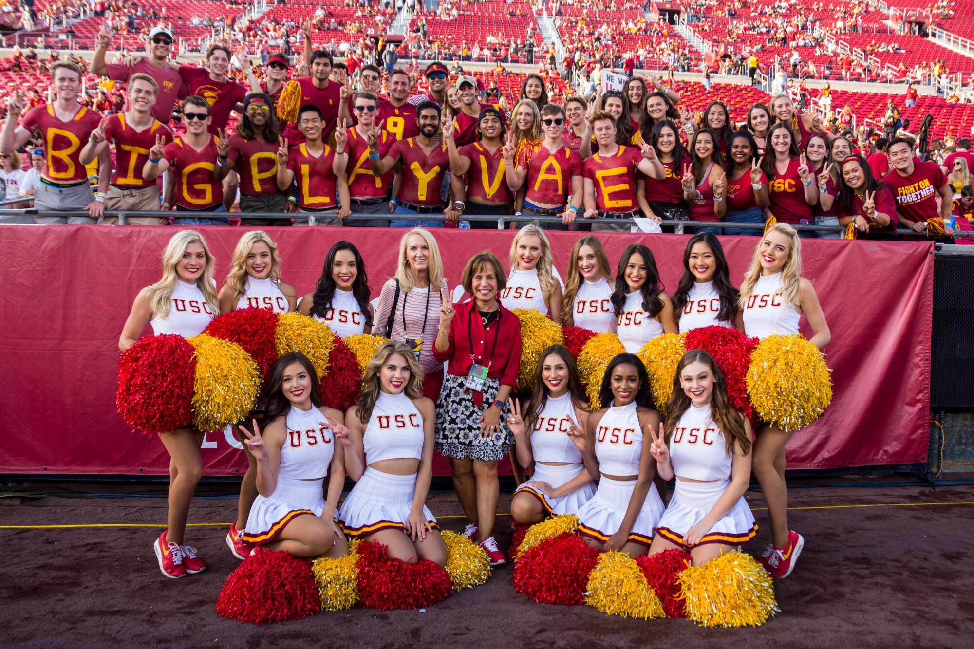 USC President Carol Folt (in red, center) poses with Lori Nelson (pink blouse) and the USC Song Girls.