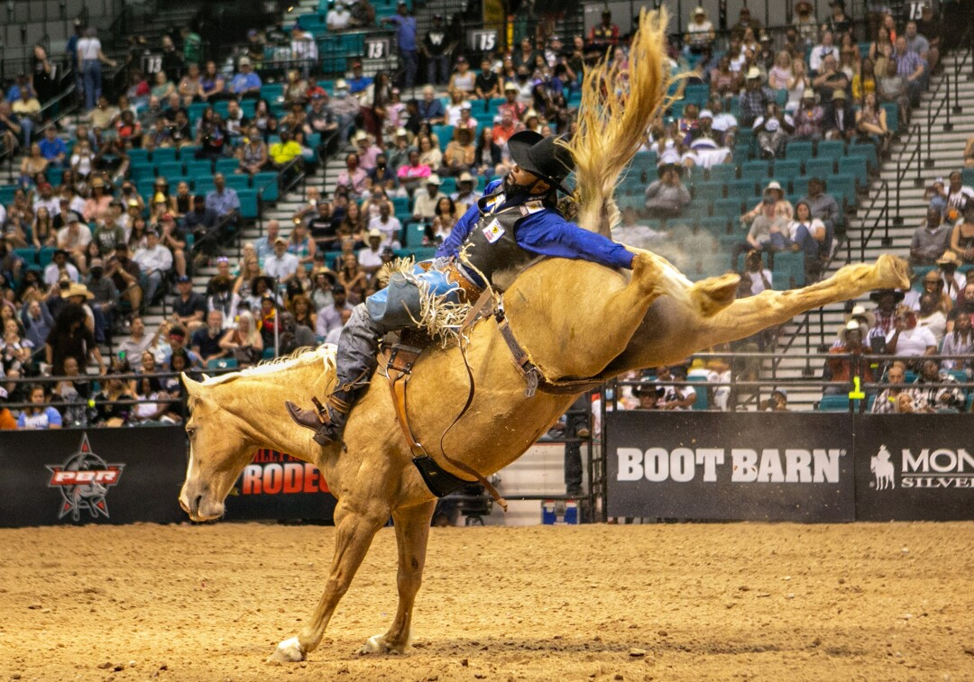 A cowboy leans back with his free arm outstretched in the finals of the bareback riding competition