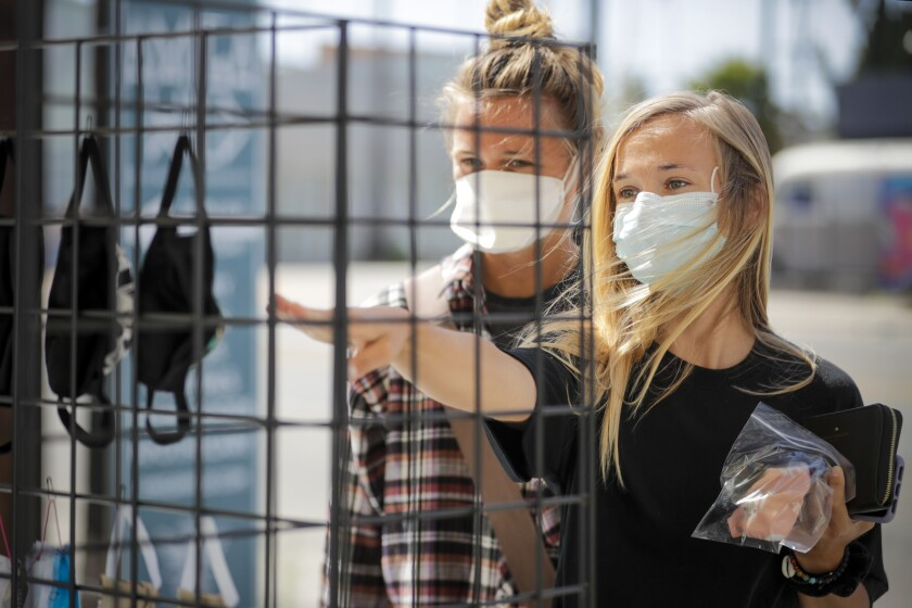 Sisters Haley Grawe, left, and Aubrey shop for face masks at a stand in front of Amiga Wild in Venice.