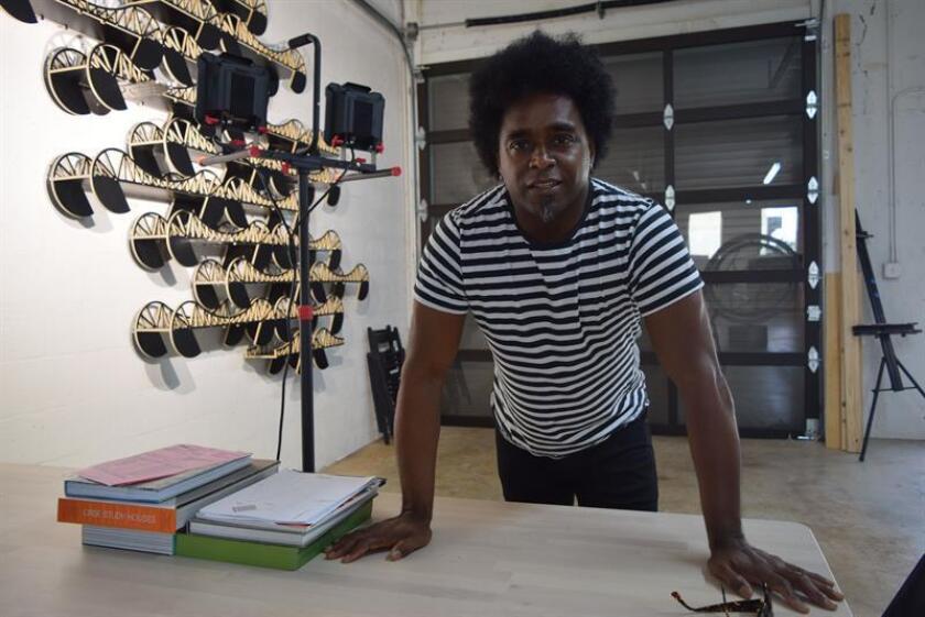 """Fotografía del 8 de diciembre de 2017 del escultor cubano Alexandre Arrechea posando junto a su obra """"Corriente"""" (2012) en su nuevo estudio de Miami (EE.UU.). EFE"""