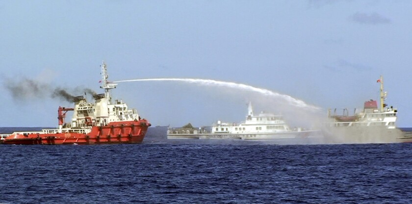 In this photo released by the Vietnam Coast Guard, a Chinese ship, left, shoots a water cannon at a Vietnamese vessel, right, while a Chinese Coast Guard ship, center, cruises alongside in the South China Sea off Vietnam's coast on Wednesday.