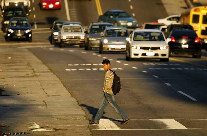 A student carefully crosses the street, but not everyone takes such precautions.