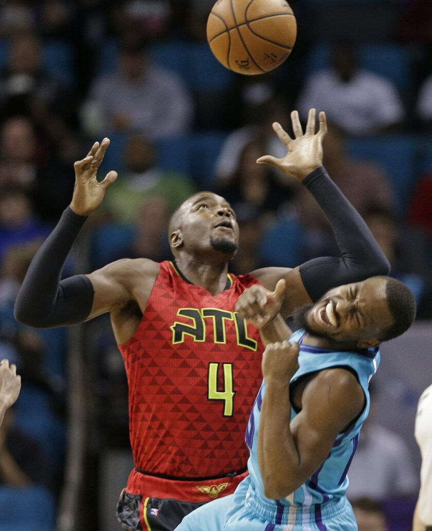 Charlotte Hornets' Kemba Walker, right, reacts after being hit by Atlanta Hawks' Paul Millsap, left, in the first half of an NBA basketball game in Charlotte, N.C., Sunday, Nov. 1, 2015. (AP Photo/Chuck Burton)