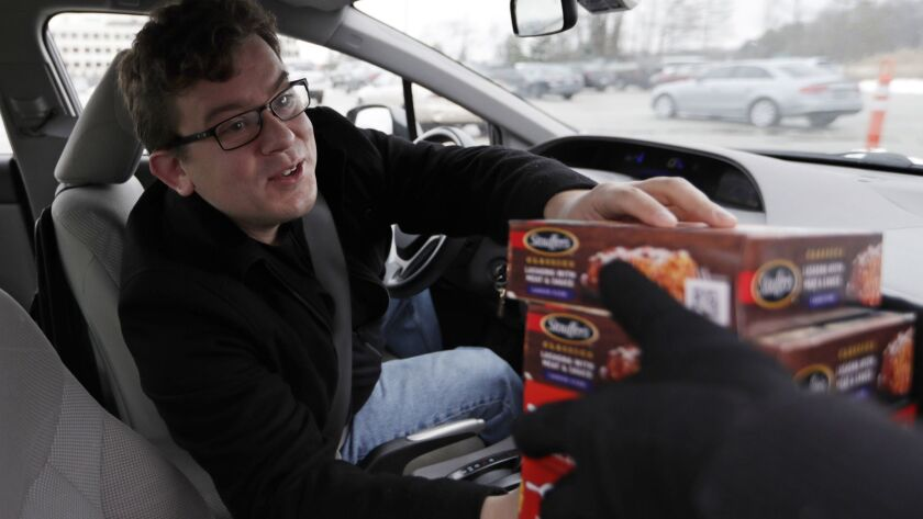 Tristan Hearn reaches for four Stouffers meals, Wednesday, Jan. 16, 2019, in Solon, Ohio. Federal wo