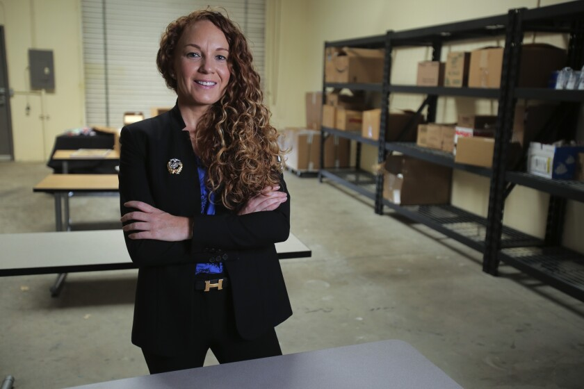 Jodie Grenier, standing with arms crossed and smiling at the camera, inside a warehouse in Vista