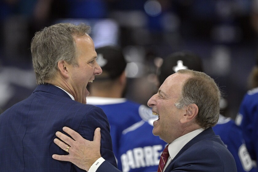 Tampa Bay Lightning head coach Jon Cooper, left, and National Hockey League Commissioner Gary Bettman are all smiles after Game 5 of the NHL hockey Stanley Cup finals against the Montreal Canadiens, Wednesday, July 7, 2021, in Tampa, Fla. (AP Photo/Phelan Ebenhack)