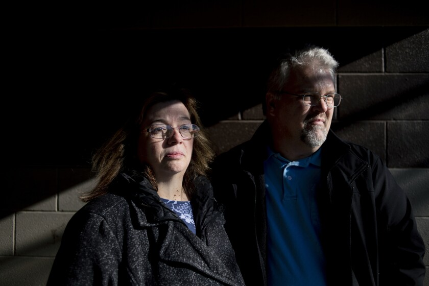 FIL E- In this Monday, Jan. 6, 2020, file photo, Pam and Karl Bacon pose for a picture at Elms Park in Swartz Creek, Mich., days after their son Kevin Bacon, of Swartz Creek, was found dead. A public defender filed a notice to seek an insanity defense for Mark Latunski, a mid-Michigan man accused in the slaying and mutilation of Kevin Bacon he met online. Shiawassee County Court documents say attorney Douglas Corwin also filed a motion Tuesday afternoon for a forensic evaluation for Mark Latunski, WNEM-TV reported. (Jake May/The Flint Journal via AP)