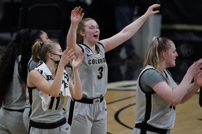 Colorado guard Frida Formann, center, celebrates with teammates Zuzanna Kulinska, left, and Charlotte Whittaker after overtime of an NCAA college basketball game against Stanford Sunday, Jan. 17, 2021, in Boulder, Colo. Colorado upset Stanford 77-72. (AP Photo/David Zalubowski)