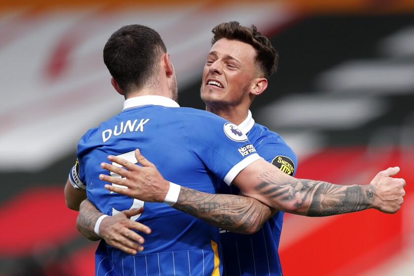 Brighton's Lewis Dunk, left and Ben White celebrate at the end of an English Premier League soccer match between Southampton and Brighton after defeating Southampton at the St Mary's Stadium in Southampton, England, Sunday March 14, 2021. (Andrew Couldridge/Pool via AP)