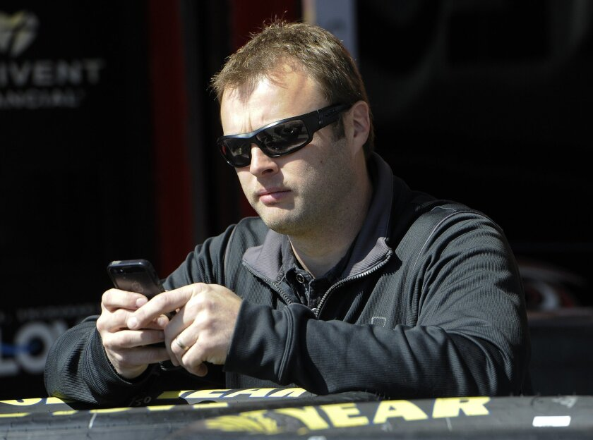NASCAR driver Travis Kvapil uses a cell phone in the garage at Atlanta Motor Speedway Friday, Feb. 27, 2015, in Hampton, Ga. Kvapil's NASCAR Sprint Cup car was stolen early Friday, forcing him to withdraw from a race this weekend at Atlanta Motor Speedway. (AP Photo/John Amis)