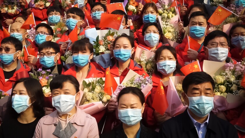 People wearing blue surgical masks hold small Chinese flags