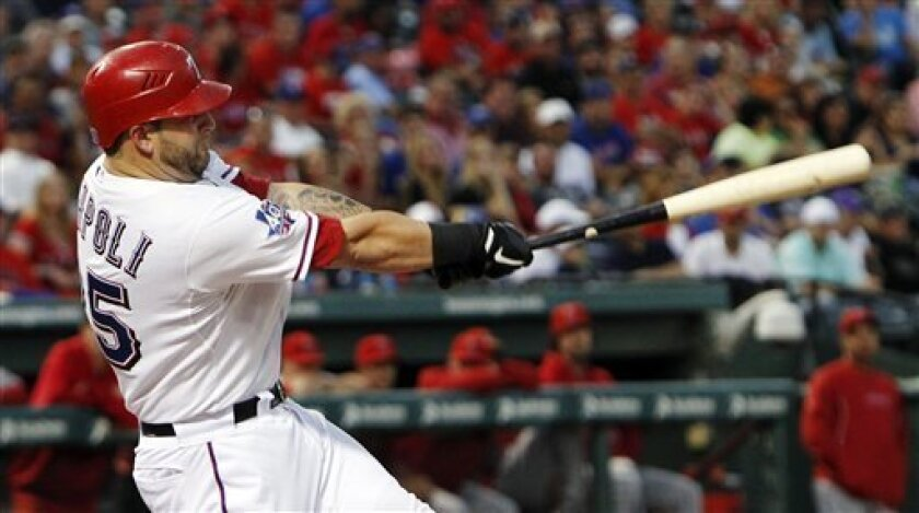 Texas Rangers' Mike Napoli hits a home run during the third inning of the second baseball game of a doubleheader against the Los Angeles Angels, Sunday, Sept. 30, 2012, in Arlington, Texas. (AP Photo/LM Otero)