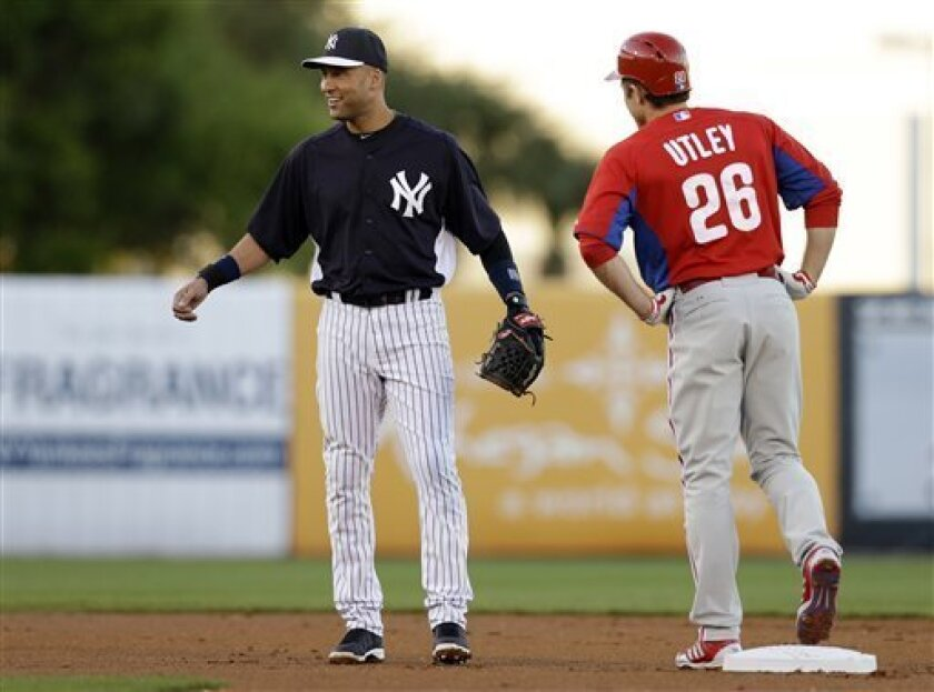 New York Yankees shortstop Derek Jeter (2) chats with Philadelphia Phillies' Chase Utley (26) in the first inning of a spring training baseball game in Tampa, Fla., Wednesday, March 13, 2013. (AP Photo/Kathy Willens)