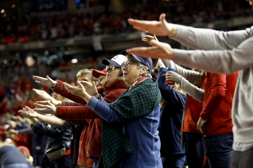 """Washington fans do the """"Baby Shark"""" gesture as the Nationals' Gerardo Parra bats in Game 3 of the World Series."""