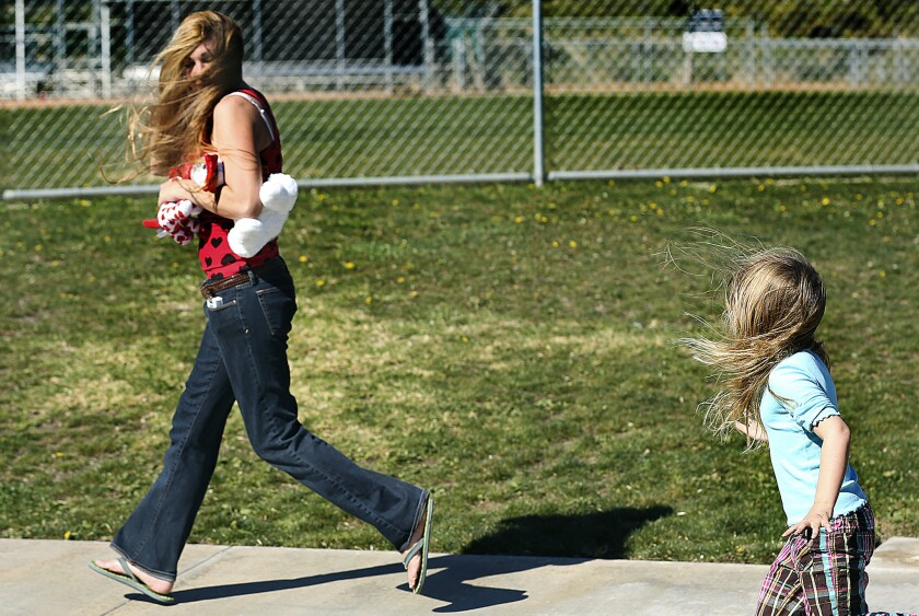 Holly Di Renzo, left, and her daughter Bella, 4, run in the wind, while playing at Lost Canyon Park in Simi Valley on a windy day in February. The National Weather Service issued a wind advisory for Los Angeles and its surrounding counties Wednesday.