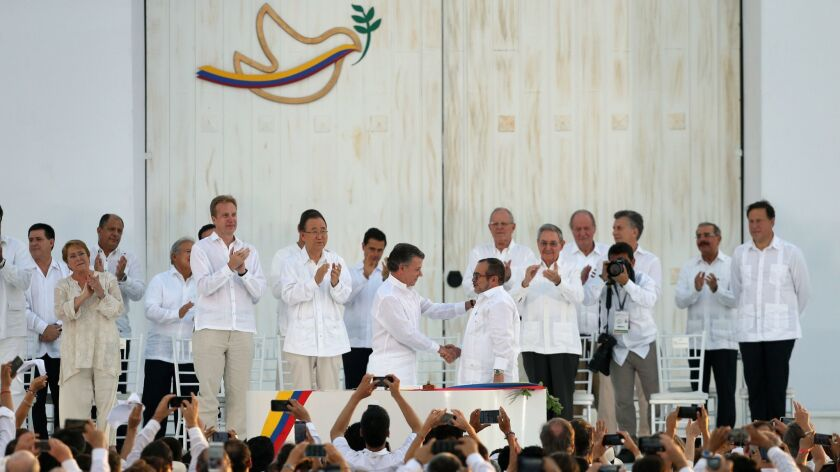 Colombia's President Juan Manuel Santos, center left, shakes hands with the top commander of the R