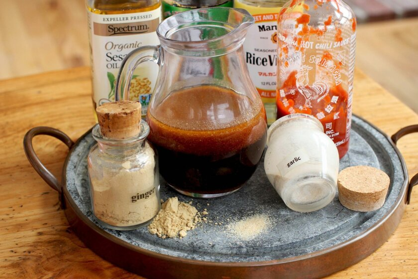 This Feb. 1, 2016 photo shows some of the ingredients for teriyaki sauce, from back left, sesame oil, ground ginger, garlic powder, rice vinegar and Sriracha hot sauce in Concord, N.H. This incredibly versatile and delicious recipe can be used on whatever protein at hand: chicken, steak, pork or sa