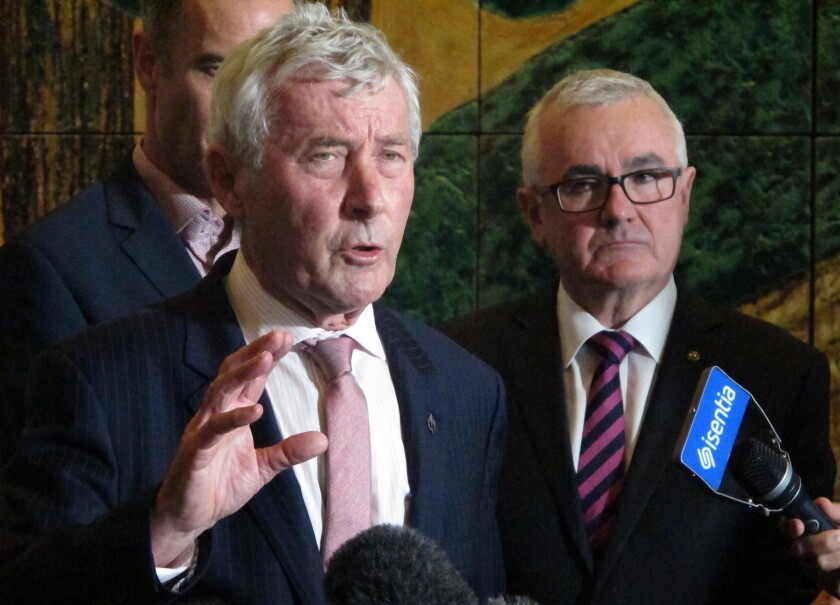 FILE - In this June 28, 2018, file photo lawyer Bernard Collaery, left, addresses the media in Parliament House in Canberra, Australia. A court agreed Wednesday, Oct. 6, 2021, to lift a shroud of secrecy from the trial of a spy's lawyer Collaery that could potentially confirm that Australia bugged East Timor's government during multibillion-dollar oil and gas negotiations. (AP Photo/Rod McGuirk, FILE)