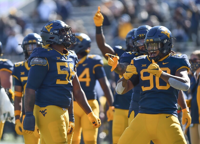 West Virginia defensive lineman Darius Stills (56) reacts after making an interception against Kansas during an NCAA college football game Saturday, Oct. 17, 2020, in Morgantown, W.Va. (William Wotring/The Dominion-Post via AP)