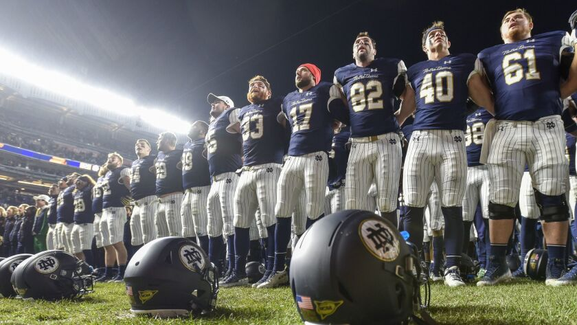 Notre Dame players line up at the end zone to greet fans and cheer with them after an NCAA college f