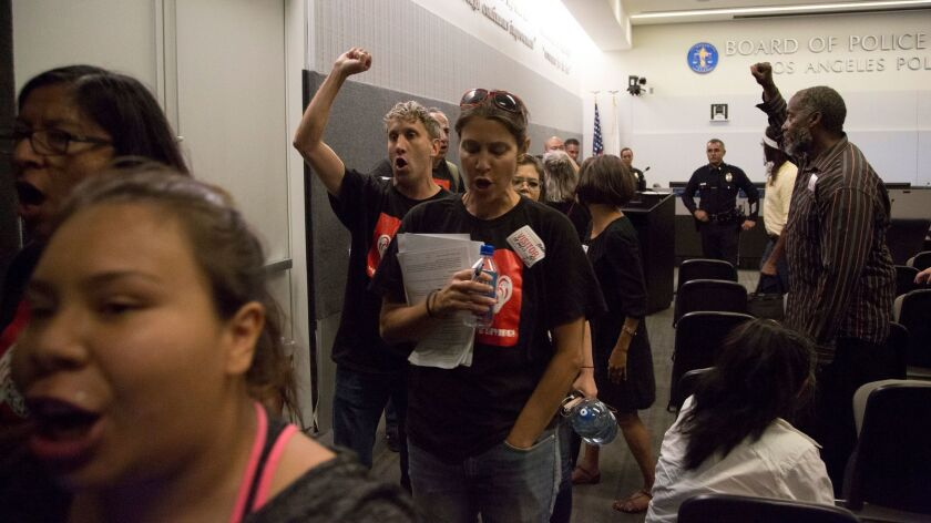 Protestors leave the L.A. Police Commission's meeting Tuesday after urging the panel to reject the L